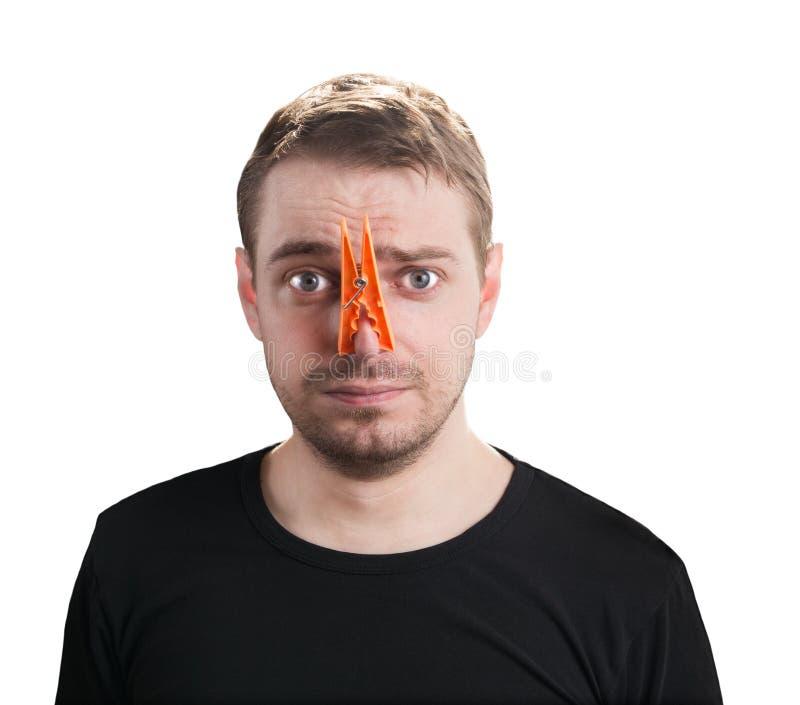 Uomo con la molletta da bucato sul suo naso. fotografia stock libera da diritti