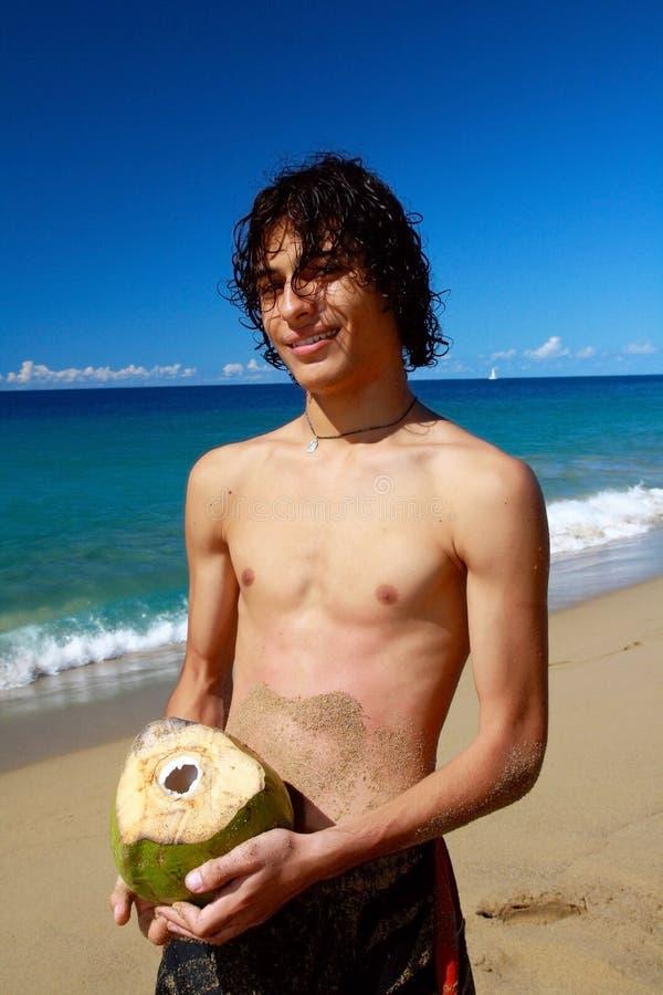 Uomo con la noce di cocco aperta sulla spiaggia dell'oceano fotografia stock