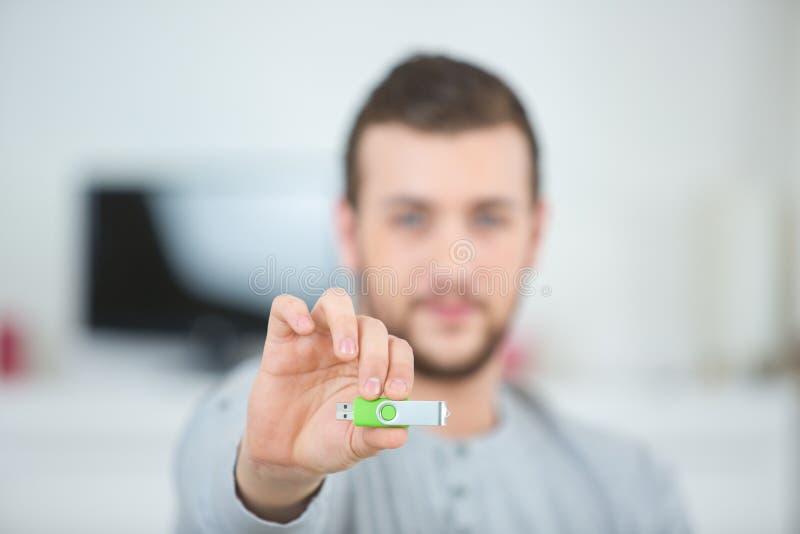 Uomo con la penna verde del usb fotografia stock