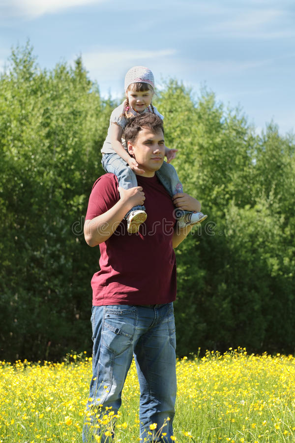 Uomo con la piccola figlia sulle spalle fra i fiori gialli fotografia stock libera da diritti