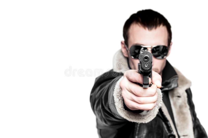 Uomo con la pistola in occhiali da sole. immagine stock