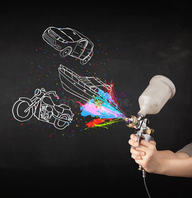 Uomo con la pittura di spruzzo dell'aerografo con il disegno dell'automobile, della barca e del motociclo fotografia stock