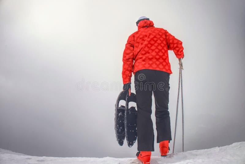 Uomo con la racchetta da neve sul percorso della neve Uomo in racchette da neve immagini stock libere da diritti