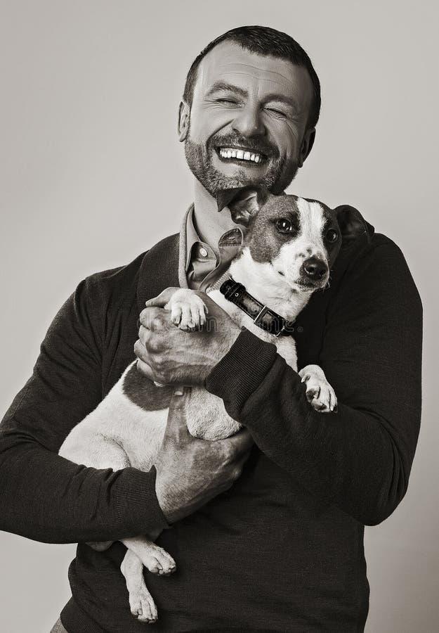 Uomo con la retro immagine del cane nella seppia immagine stock