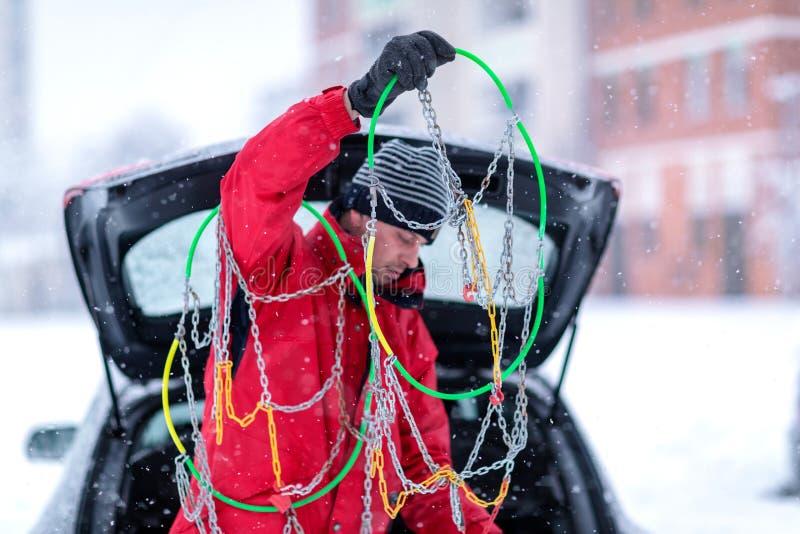 Uomo con la ripartizione della neve dell'automobile delle catene da neve fotografia stock