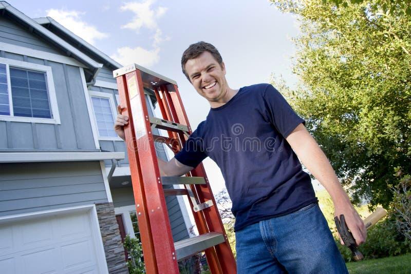 Uomo con la scaletta ed il martello fotografie stock libere da diritti