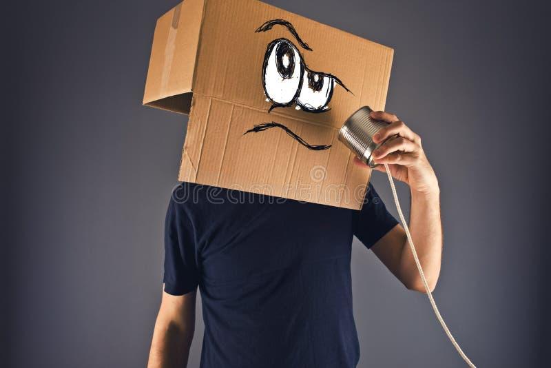 Uomo con la scatola di cartone sulla sua testa facendo uso del telefono del barattolo di latta immagine stock