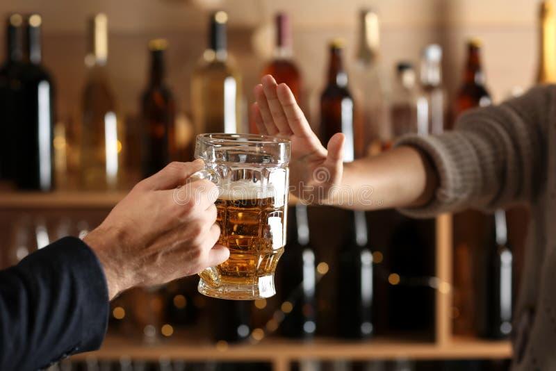 Uomo con la tazza di birra e della donna che rifiutano di bere nella barra fotografie stock libere da diritti