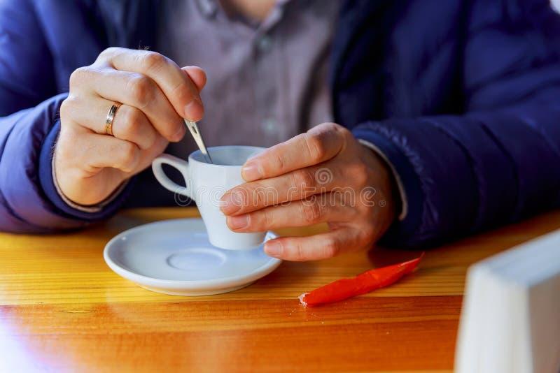 Uomo con la tazza di caffè Giovane persona di sesso maschile in abbigliamento casual che ha bevanda calda in caffè fotografia stock