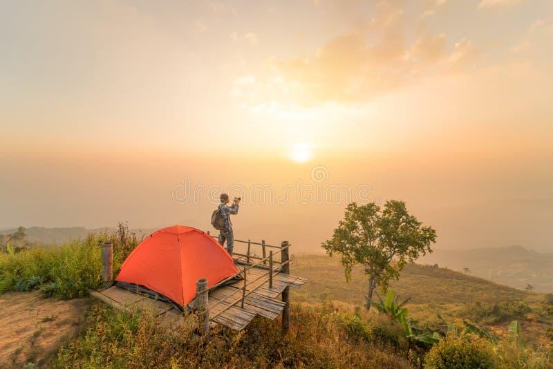 Uomo con la tenda di campeggio sulla collina con alba o il tramonto fotografie stock