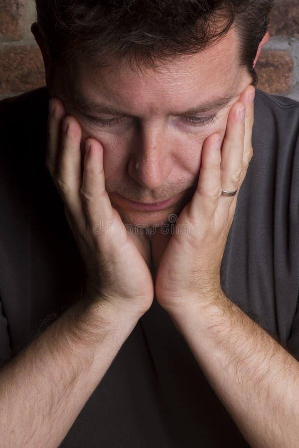 Uomo con la testa in mani fotografia stock libera da diritti