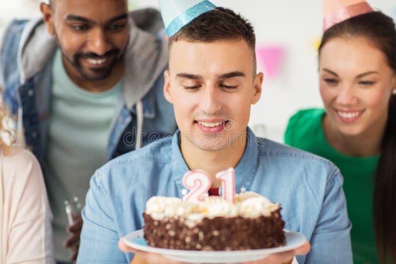 Uomo con la torta di compleanno ed il gruppo alla festa dell'ufficio fotografie stock