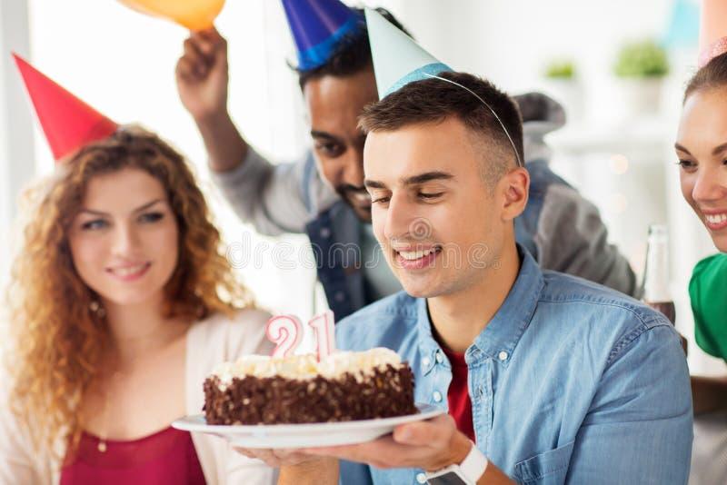 Uomo con la torta di compleanno ed il gruppo alla festa dell'ufficio immagini stock libere da diritti