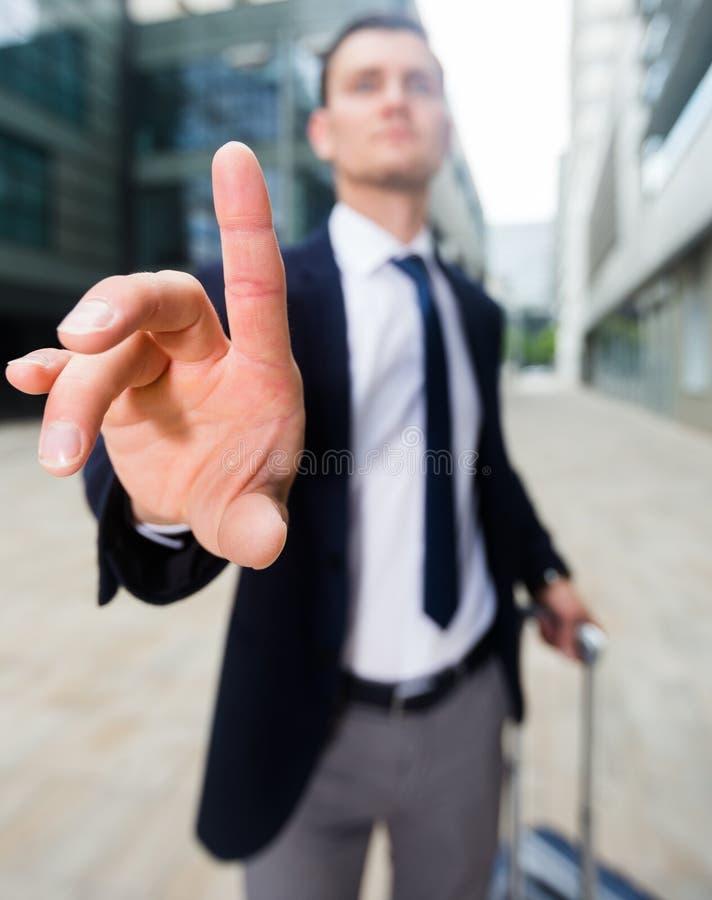 Uomo con la valigia che chiede al compagno di aspettare fotografia stock libera da diritti