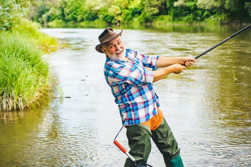 Uomo con le canne da pesca sull'ancoraggio del fiume angler La pesca con la mosca è più rinomata come metodo per la cattura la tr fotografie stock libere da diritti
