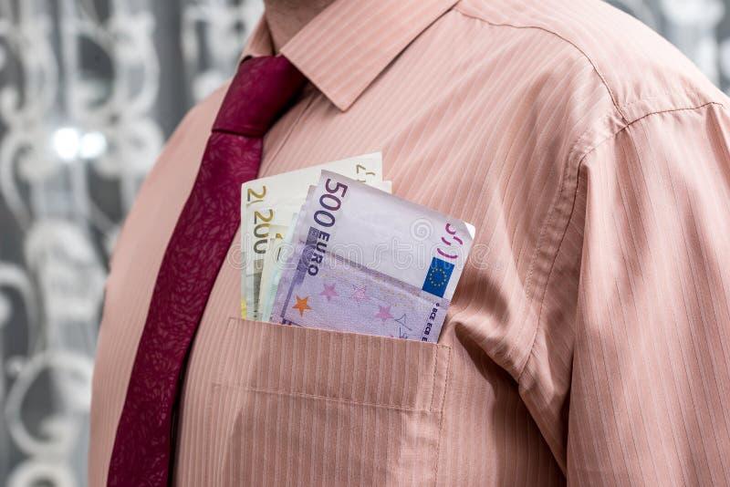Uomo con le euro banconote in sua tasca della camicia fotografia stock libera da diritti