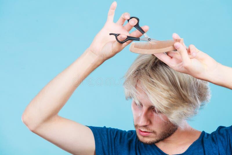 Uomo con le forbici e pettine che creano nuova pettinatura fotografia stock libera da diritti