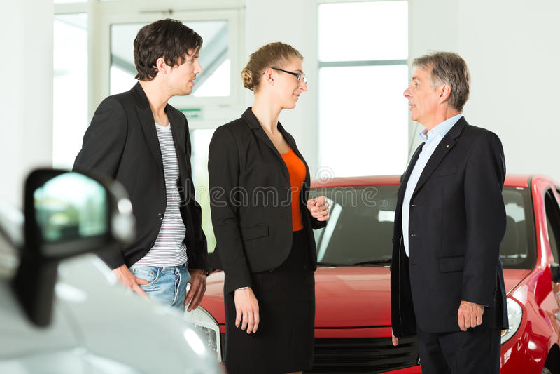 Uomo con le giovani coppie nel concessionario auto immagini stock