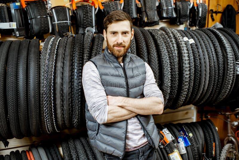 Uomo con le gomme della bicicletta nel negozio immagine stock