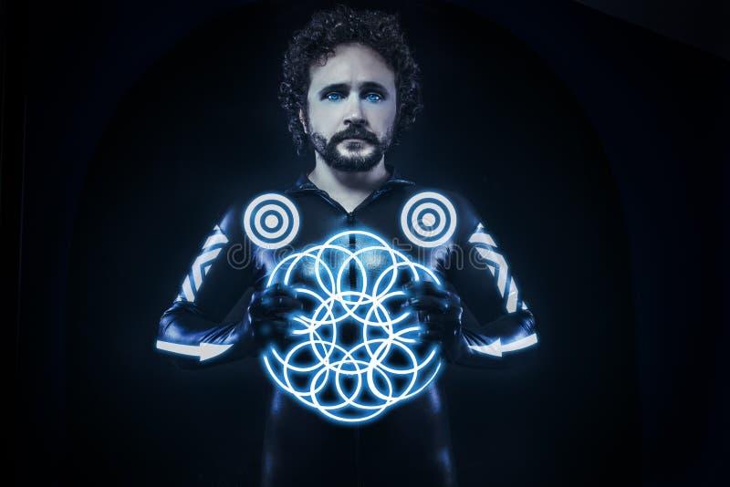 Uomo con le luci al neon blu, il costume futuro del guerriero, fantasia s immagine stock