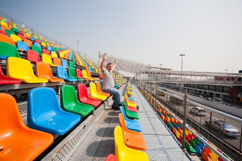 Uomo con le mani su nei sedili per gli spettatori immagine stock libera da diritti