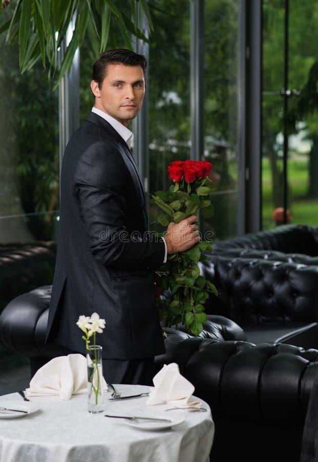 Uomo con le rose in ristorante fotografia stock