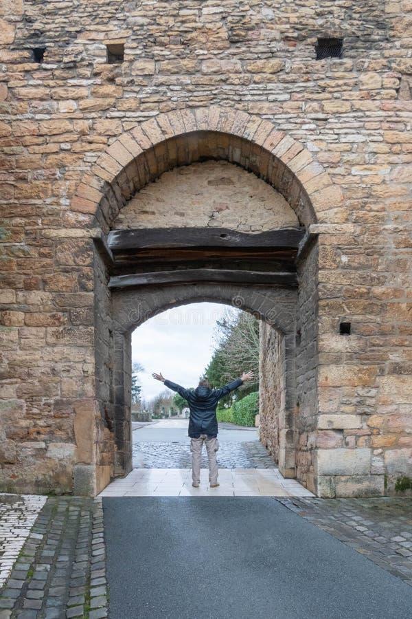Uomo con le sue armi spalancate nella entrata della parete Francia dell'abbazia di Cluny fotografie stock