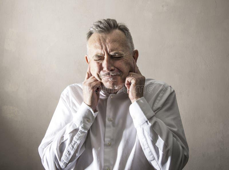 Uomo con le sue dita in sue orecchie per non sentire fotografia stock