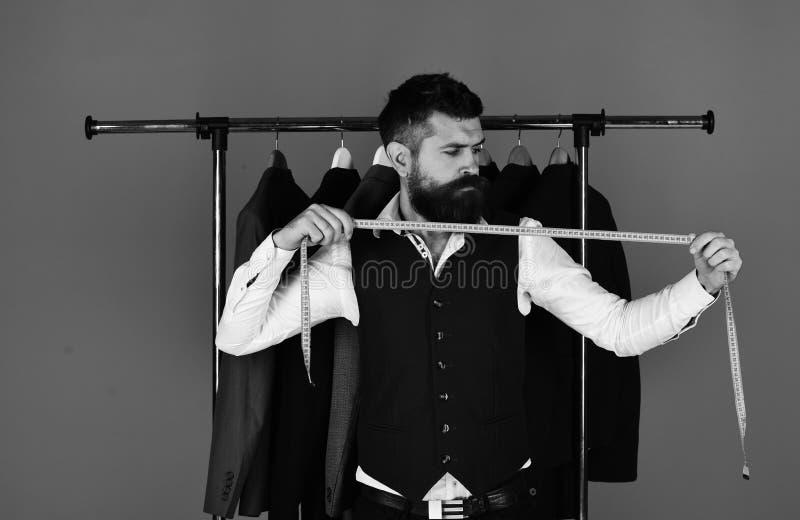 Uomo con le tenute della barba che misurano nastro Il sarto taglia e cuce il vestito Giovane nell'adattamento del negozio fotografia stock
