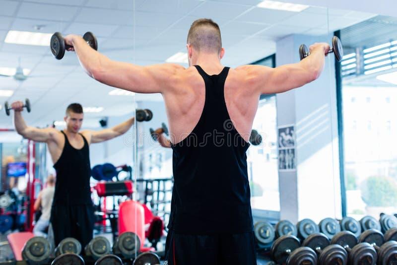 Uomo con le teste di legno allo sport nella palestra di forma fisica fotografia stock libera da diritti