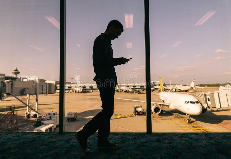 Uomo con lo smartphone all'aeroporto immagini stock libere da diritti