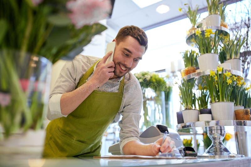 Uomo con lo smartphone che fa le note al negozio di fiore immagine stock libera da diritti