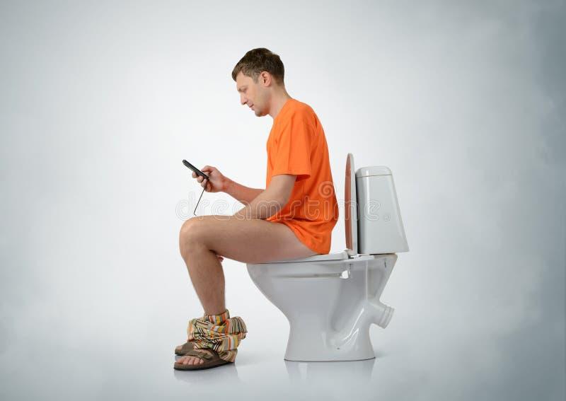 Uomo con lo smartphone che si siede sulla toilette fotografie stock libere da diritti