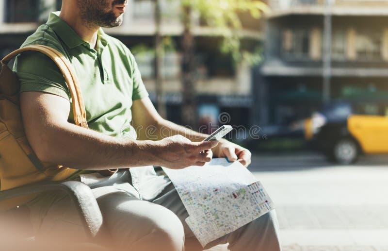 Uomo con lo smartphone giallo della tenuta dello zaino, città di sguardo turistica della mappa sul taxi del fondo, itinerario di  immagini stock libere da diritti