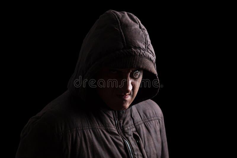 Uomo con rabbia repressa ed istinto violento che si nascondono nelle ombre immagine stock libera da diritti