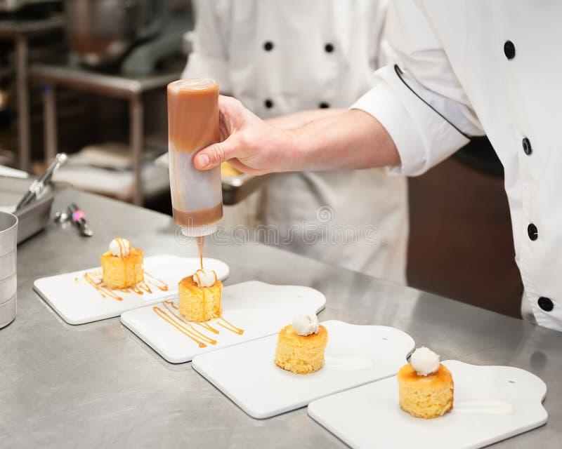 Uomo con salsa di pioviggine del caramello della cucina sui piccoli dolci completati con crema immagini stock libere da diritti