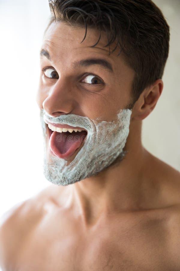 Uomo con schiuma sul fronte che mostra il suo tonque immagini stock