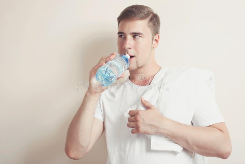 Uomo con un asciugamano bianco e una bottiglia di acqua fotografie stock