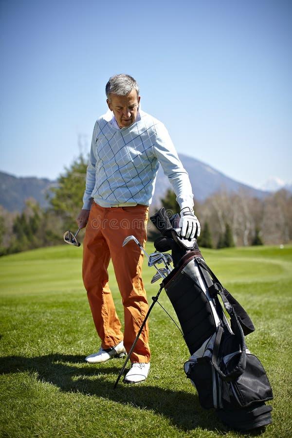 Uomo con un club di golf e un sacchetto immagine stock
