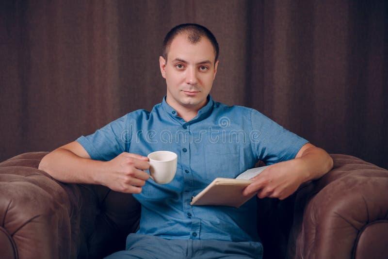 Uomo con un libro e una tazza di caffè in sue mani che si siedono in una poltrona ed in una lettura psicologo immagine stock libera da diritti