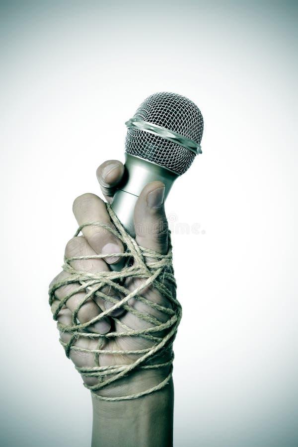 Uomo con un microfono legato con la corda fotografia stock libera da diritti