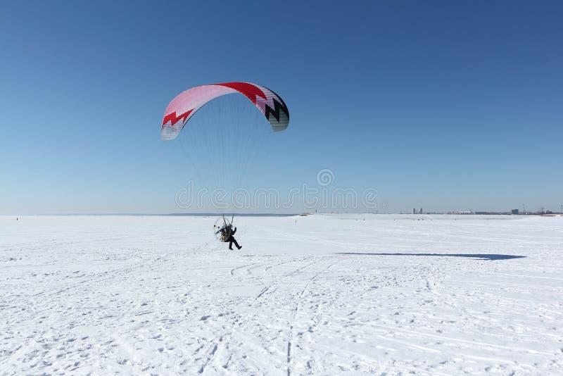 Uomo con un paracadute e un motore, volanti nel cielo su un inverno immagine stock