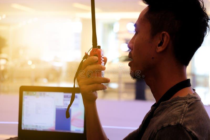 Uomo con un walkie-talkie o un ricetrasmettitore radiofonico portatile immagine stock