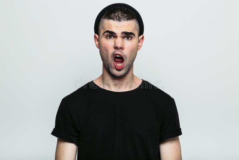 Uomo con una bocca aperta che esamina macchina fotografica fotografia stock