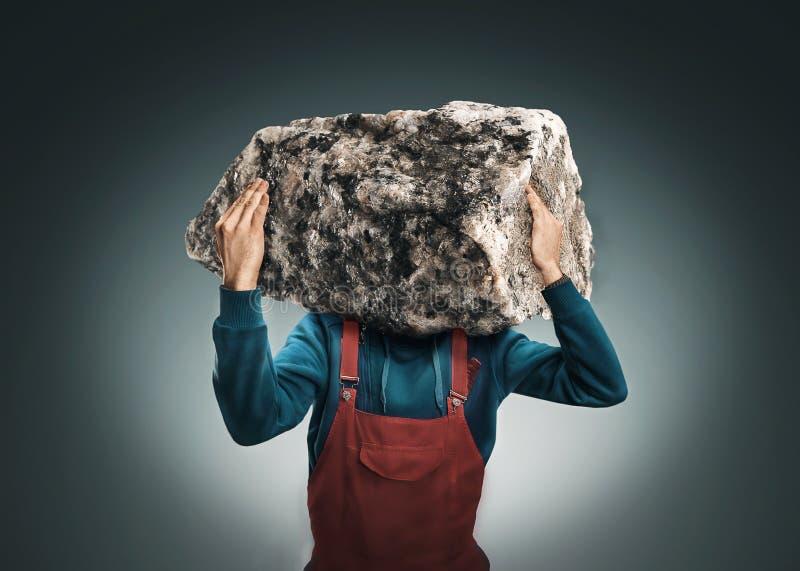 Uomo con una grande roccia immagine stock libera da diritti