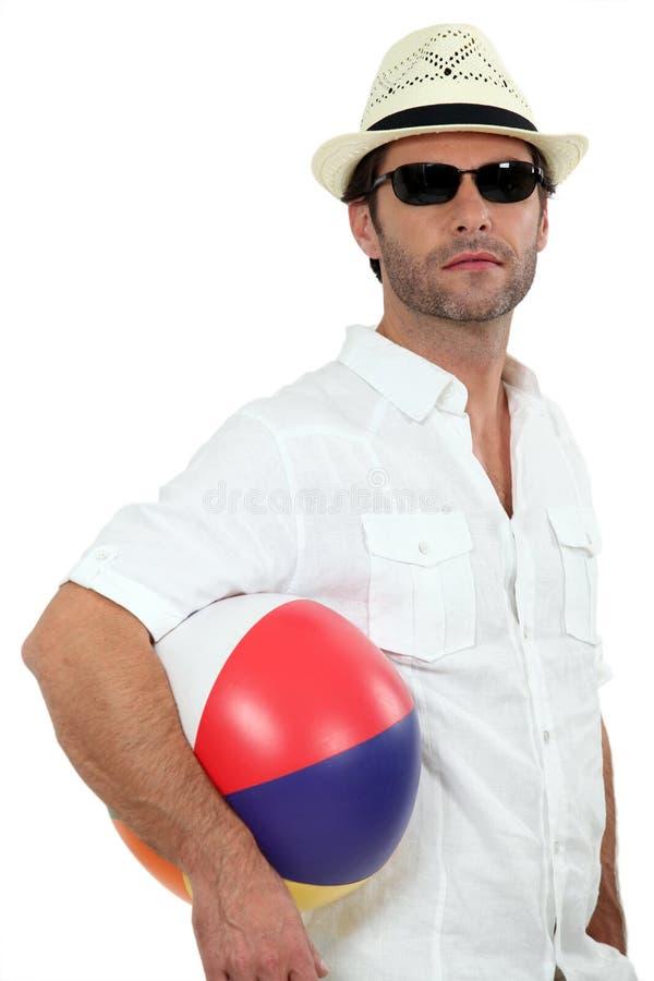 Uomo con una sfera di spiaggia fotografia stock libera da diritti