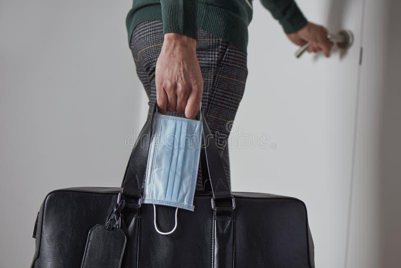 Uomo con una valigia e una maschera chirurgica immagini stock libere da diritti