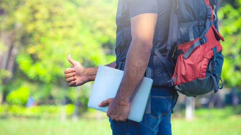 Uomo con uno zaino che sta in un parco Viaggiatore con zaino e sacco a pelo che tiene un computer portatile Concetto del nomade d fotografia stock libera da diritti