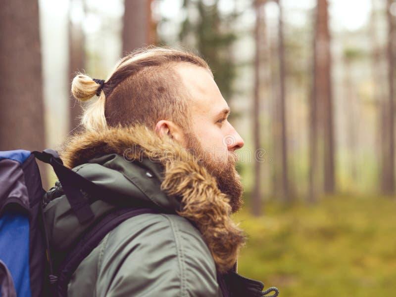 Uomo con uno zaino e una barba che fanno un'escursione nella foresta immagini stock libere da diritti