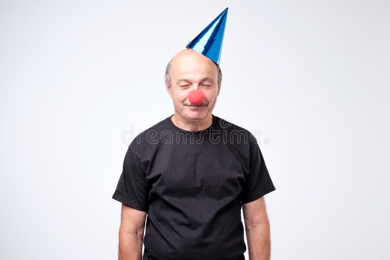 Uomo confuso sugli sguardi del cappello del pagliaccio con l'espressione titubante fotografia stock libera da diritti